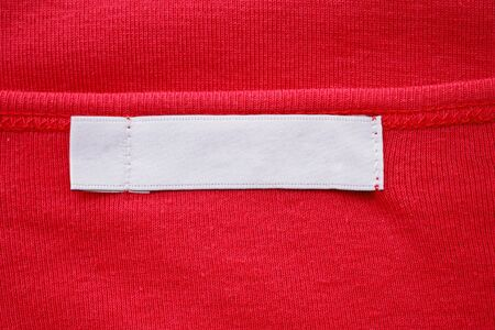 Blank white clothes tag label on new red shirt Фото со стока