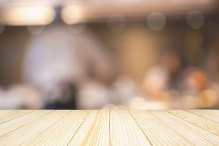 Leere Holztischplatte mit Küchenchef, der in der Restaurantküche kocht, abstrakt, unscharf, defokussiert