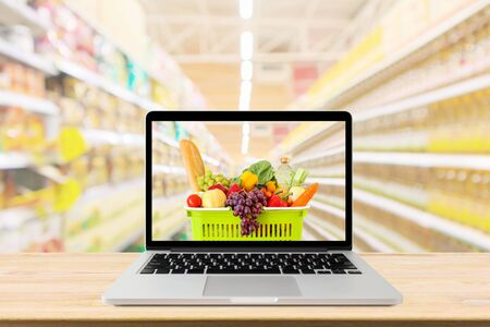 Allée de supermarché arrière-plan flou avec ordinateur portable et panier sur table en bois concept en ligne d'épicerie