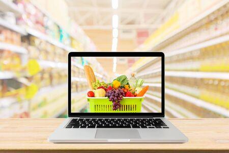 Pasillo del supermercado fondo borroso con ordenador portátil y carrito de la compra en la mesa de madera concepto online de abarrotes