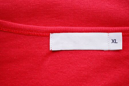 Blank white clothes tag label with XL size on new red shirt Zdjęcie Seryjne