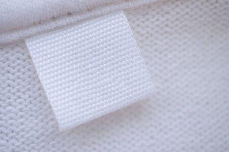 Blank white clothes label on new shirt background Zdjęcie Seryjne