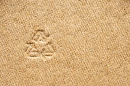 recycle sign on brown cardboard paper texture background
