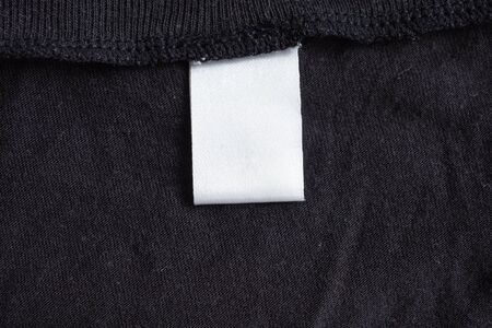 Blank white laundry care clothing label on black fabric texture