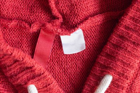 Blank white laundry care clothing label on red knitted texture background