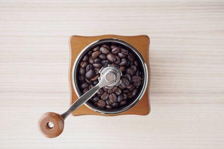Vintage manual coffee grinder with roasted coffee beans