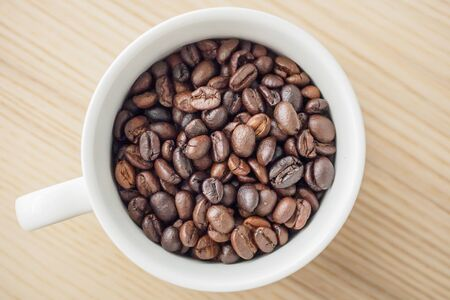 fresh roasted coffee beans in white cup on wood table, top view