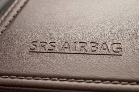 airbag safety sign on brown leather texture in modern car