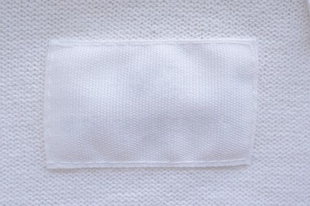 Blank white clothes label on new shirt background Banco de Imagens