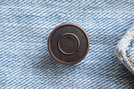 Metal button on blue denim jeans background Stock fotó