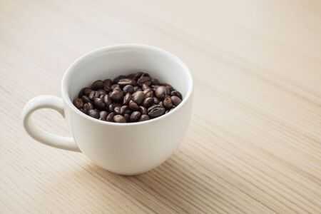 fresh roasted coffee beans in white cup on wood table