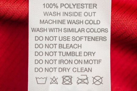 White laundry care washing instructions clothes label on red jersey polyester sport shirt