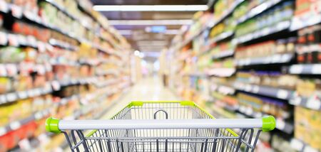 Empty green shopping cart with supermarket aisle interior with product shelves abstract blur background Reklamní fotografie
