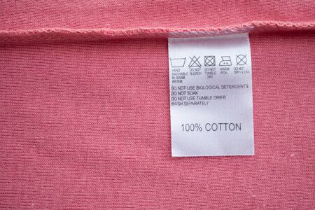 White laundry care washing instructions clothes label on cotton shirt