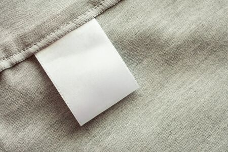 White blank laundry care clothing label on gray fabric texture background