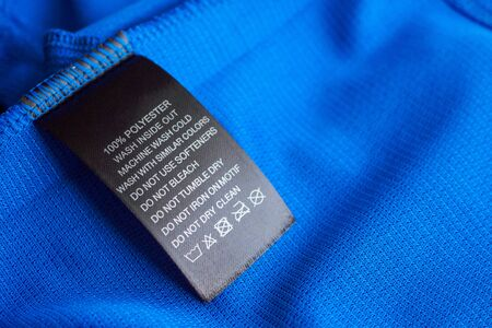 Black laundry care washing instructions clothes label on blue jersey polyester sport shirt
