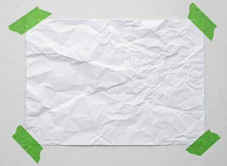 blank note paper with adhesive tape on white wall
