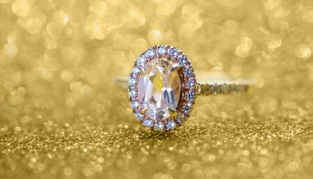 Jewelry diamond ring with abstract festive gold glitter Christmas holiday texture background blur with bokeh light Zdjęcie Seryjne