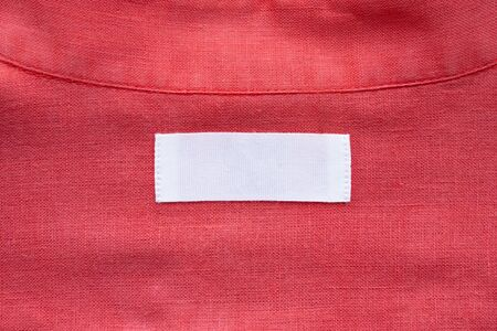 White blank clothing tag label on red linen shirt fabric texture background Stockfoto