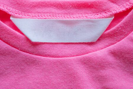 blank laundry care clothes label on pink shirt Stockfoto