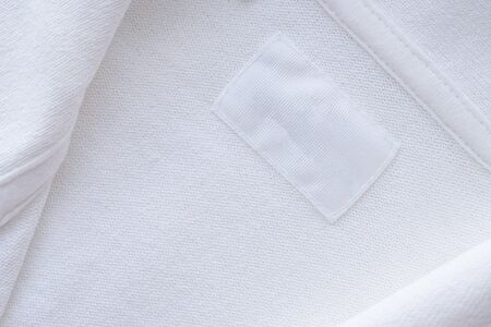 Blank white clothes label on new shirt background Stockfoto