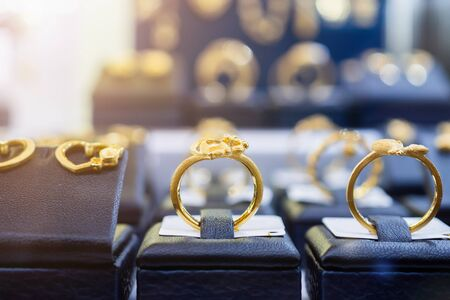 Jewelry golden rings earrings and necklaces show in luxury retail store window display showcase Stockfoto