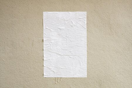 Blank white crumpled and creased adhesive street poster mockup on concrete wall background Imagens