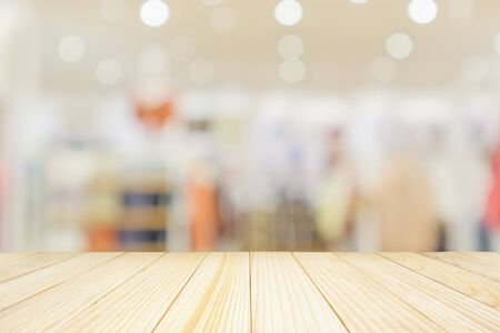 Empty wood table top with modern clothing store interior blur abstract defocused background with bokeh light for product display