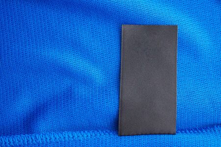 Black blank laundry care clothes label on blue jersey polyester sport shirt background