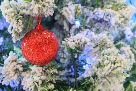 Christmas tree decorated with red ball on pine branches background