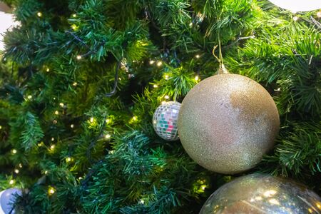 Christmas tree decorated with golden ball on pine branches background