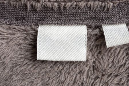 Blank white laundry care clothing label on fur texture background