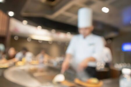 Chef cooking in restaurant kitchen abstract blurred defocused background