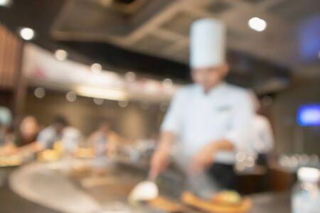Szef kuchni gotuje w kuchni restauracji streszczenie niewyraźne tło niewyraźne
