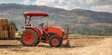 tractor in agriculture field with mountain and blue sky