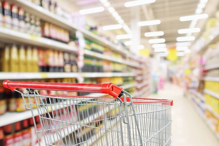 Empty shopping cart with abstract blur supermarket discount store aisle and sauce seasoning product shelves interior defocused background