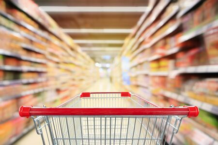 Empty red shopping cart with supermarket aisle interior with product shelves abstract blur background