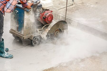 Worker using diamond saw blade machine cutting concrete road at construction site