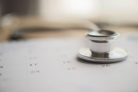 Stethoscope with calendar page date on wood table background doctor appointment medical concept 免版税图像 - 150252965