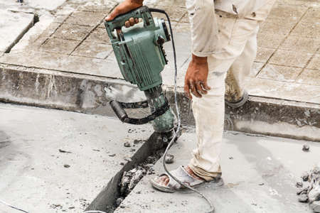 Construction worker using jackhammer drilling concrete surface
