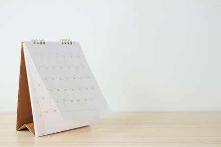 Calendar page flipping sheet on wood table background business schedule planning appointment meeting concept