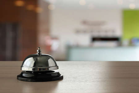 Hotel service bell on wood counter background Foto de archivo
