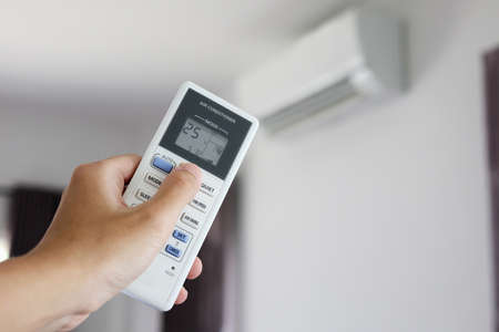 Hand with remote control directed on air conditioner inside the room