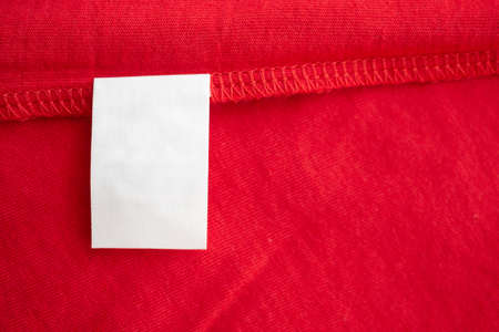 White laundry care washing instructions clothes label on red cotton shirt