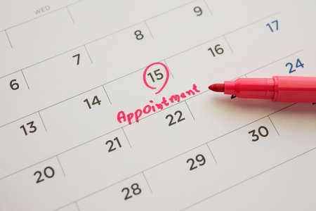Red color marker pen pointing at important appointment schedule on white calendar page date close up