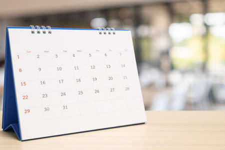 white paper desk calendar on wood table with blurred bokeh background appointment and business meeting concept