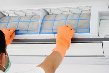 Asian man cleaning air conditioner dirty filter