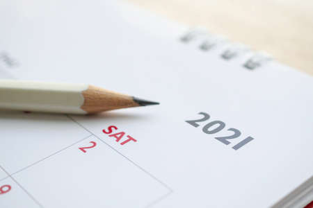 white pencil on 2021 calendar background business planning appointment meeting concept