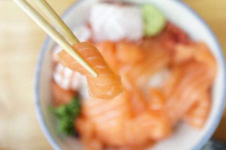 Asian woman eating salmon slice sashimi with rice in Japanese restaurant