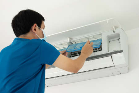 Asian man cleaning air conditioner filter